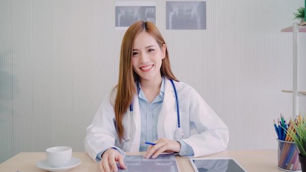 Doctor de sexo femenino asiático confiado que se sienta en el escritorio de oficina y que sonríe en la cámara Foto gratis