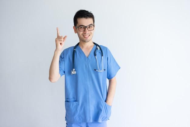 Doctor de sexo masculino joven sonriente que señala hacia arriba Foto gratis