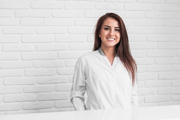 Doctor sonriente sentado delante de la pared de ladrillos blancos Foto gratis