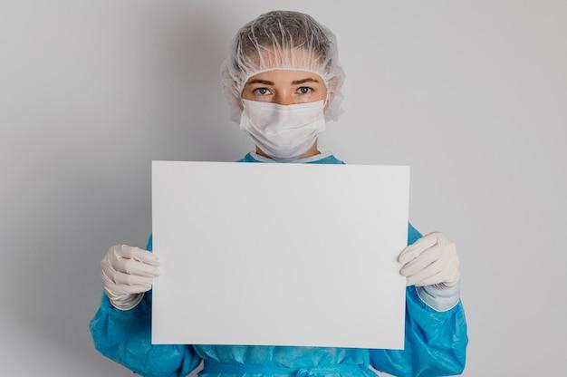 Doctor sosteniendo un cartel en blanco Foto gratis