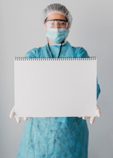 Doctor sosteniendo una tarjeta en blanco Foto gratis