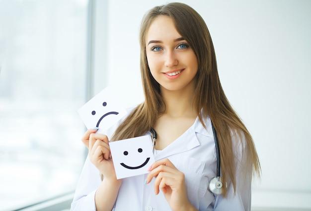 Doctor sosteniendo una tarjeta con el símbolo sonrisa, concepto médico Foto Premium
