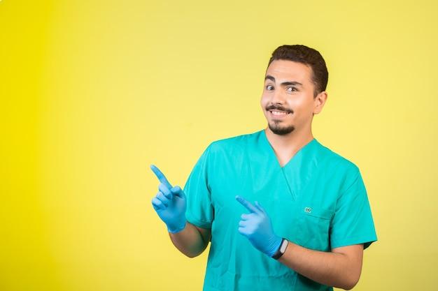 Doctor en uniforme y máscara de mano apuntando algo arriba. Foto gratis
