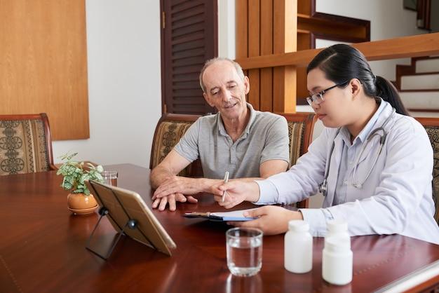 Doctora asiática hablando con paciente caucásico senior durante visita a domicilio Foto gratis
