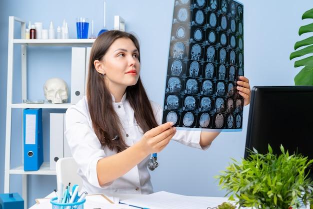 Doctora examinando la imagen de mr del paciente en su consultorio Foto Premium