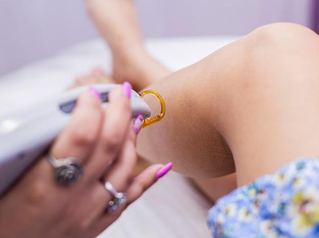 Una doctora está haciendo una depilación láser en la piel de las piernas de una mujer. Foto gratis