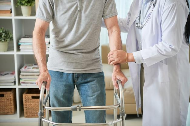 Doctora irreconocible ayudando a paciente masculino a caminar con bastidor Foto gratis
