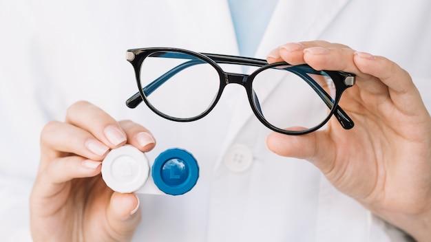 Doctora mostrando un par de anteojos y lentes de contacto Foto Premium
