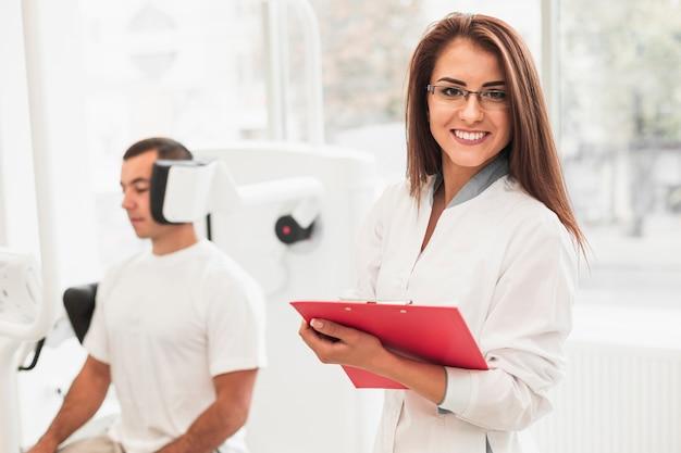Doctora sosteniendo portapapeles y mirando al fotógrafo Foto gratis