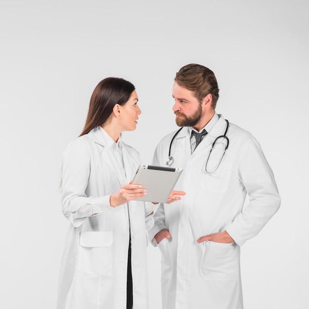 Doctores de sexo femenino y masculino discutiendo y mirándose unos a otros. Foto gratis