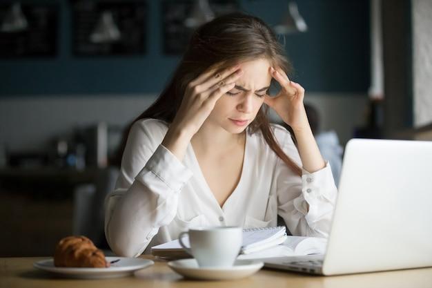 Dolor de cabeza subrayado nervioso del estudiante femenino que siente en café Foto gratis
