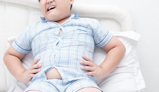 Dolor de estómago obeso niño obeso en la cama Foto Premium