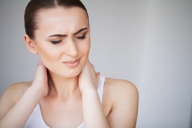 Dolor. hermosa joven se siente enferma y tiene un dolor en el cuello Foto Premium
