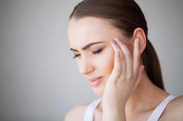 Dolor. retrato de una mujer joven tiene dolor de cabeza Foto Premium