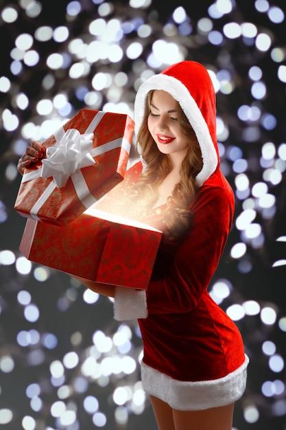 Doncella de nieve en traje rojo con un regalo para año nuevo Foto gratis