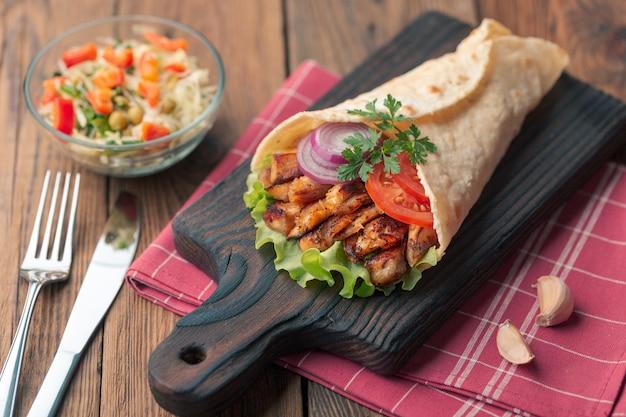 Doner kebab está acostado en la tabla de cortar. shawarma con carne de pollo, cebolla, ensalada se encuentra en una vieja mesa de madera oscura. Foto Premium