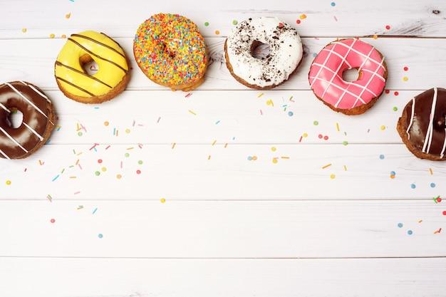 Donuts y confeti en una mesa de madera con espacio para su texto. Foto Premium