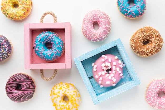 Donuts lindos en cajas de colores Foto gratis