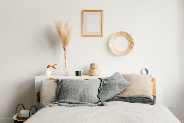 Dormitorio en un estilo natural minimalista escandinavo. almohadas grises en la cama. decoración encima de la cama Foto Premium