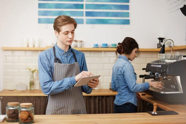 Dos alegres baristas con elegante uniforme de trabajo en la barra del bar. Foto gratis