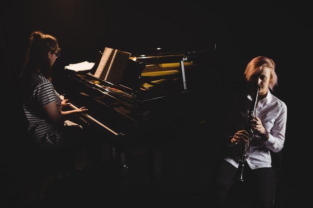 Dos alumnas tocando clarinete y piano Foto gratis