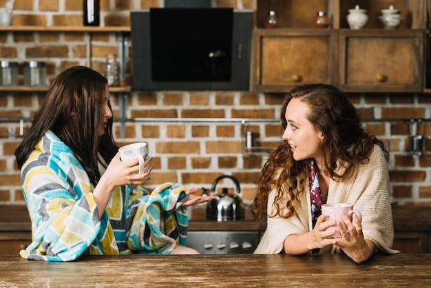 Dos amigas bebiendo una taza de café en la cocina Foto gratis