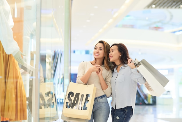 Dos amigas escaparates en el centro comercial en venta Foto gratis