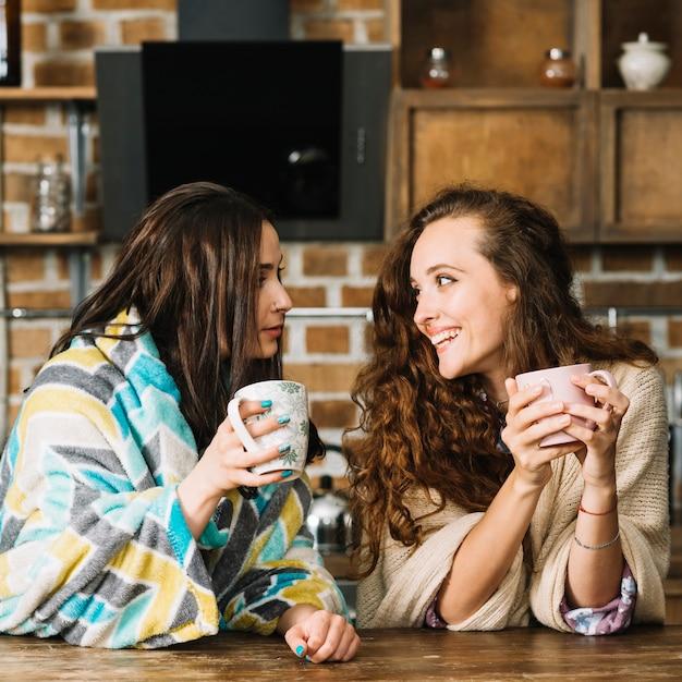 Dos amigas mirándose mientras beben una taza de café Foto gratis