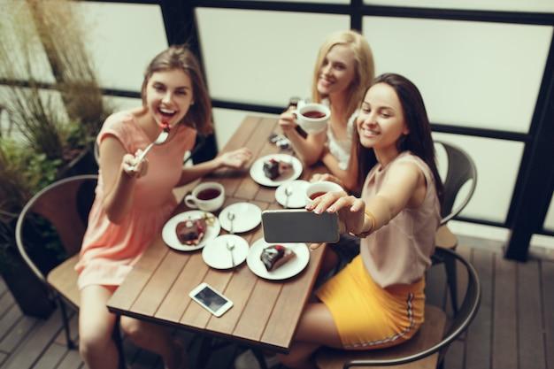 Dos amigas pasan tiempo juntas tomando café en la cafetería, desayunando y postre. Foto gratis