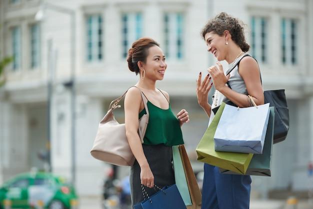 Dos amigas de pie en la calle con bolsas de compras y charlando Foto gratis