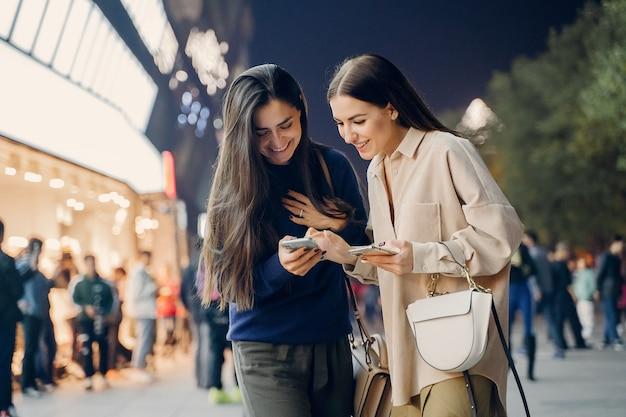 Dos amigas usando su teléfono celular mientras exploran una nueva ciudad por la noche Foto gratis