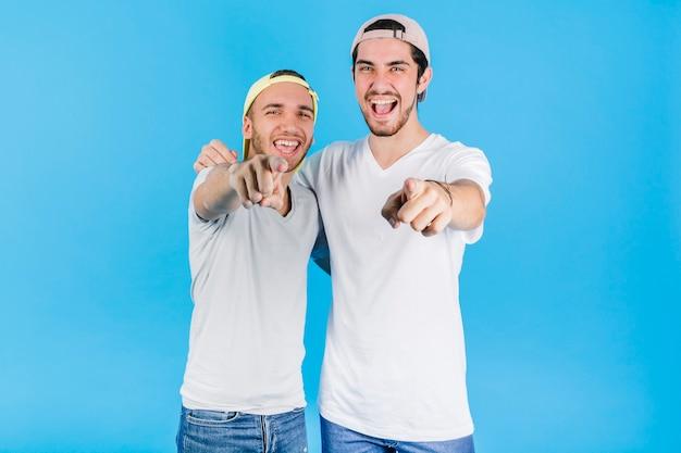 Dos amigos alegres apuntando a la cámara Foto gratis