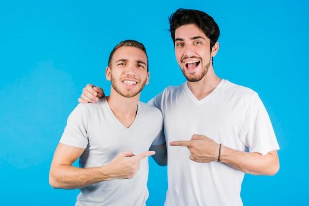 Dos amigos alegres apuntándose el uno al otro Foto gratis