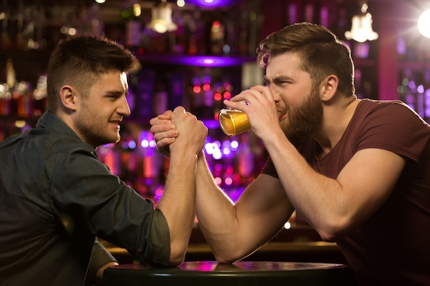 Dos amigos bebiendo cerveza y divirtiéndose en el pub Foto gratis