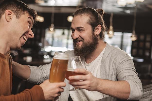Dos amigos conversando con cerveza en el pub Foto Premium