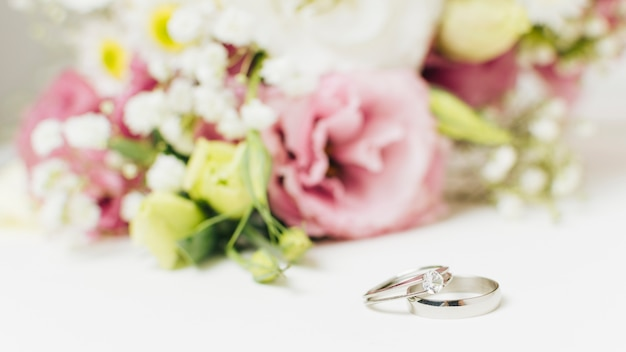 Dos anillos de bodas de plata cerca del ramo de flores. Foto gratis