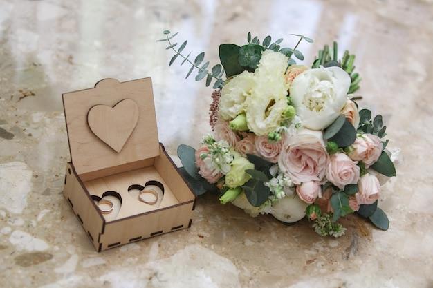 Dos anillos de oro en una hermosa caja de madera. ramo de flores rosas y blancas. día de la boda. detalles de la boda. Foto Premium