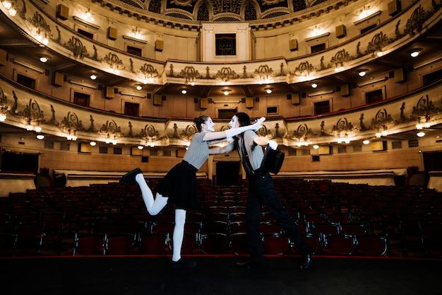 Dos artistas mimos actuando en el escenario en un auditorio vacío Foto gratis