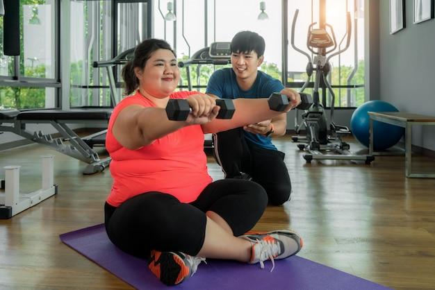 Dos asiático entrenador hombre y mujer con sobrepeso haciendo ejercicio con pesas juntos en el moderno gimnasio, feliz y sonríe durante el entrenamiento. las mujeres gordas cuidan la salud y quieren perder el concepto de peso. Foto Premium