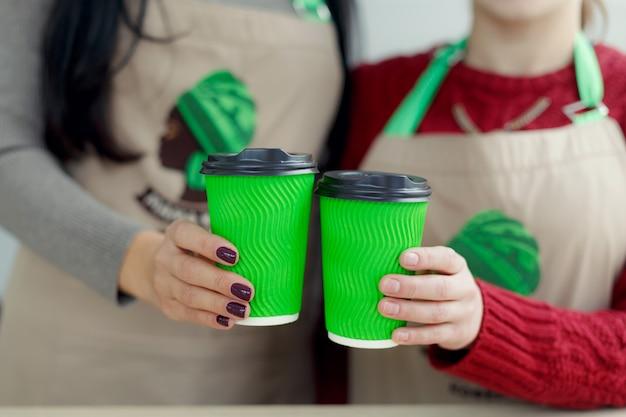 Dos baristas en delantales sostiene café caliente en una taza de papel para llevar verde Foto Premium