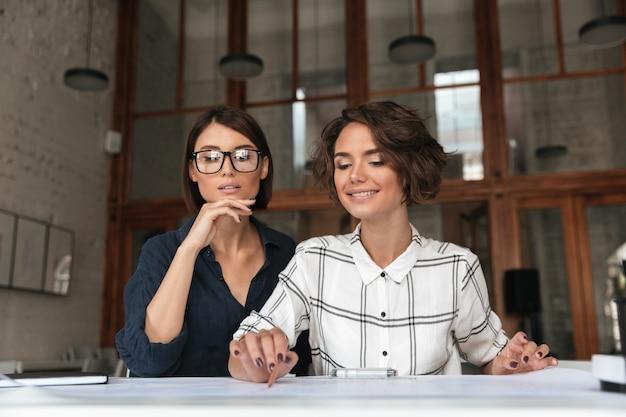 Dos bellas mujeres muy sonrientes sentados a la mesa Foto gratis