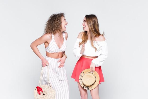 Dos blogueras jóvenes hablan sobre viajes en vivo, en blanco. Foto Premium
