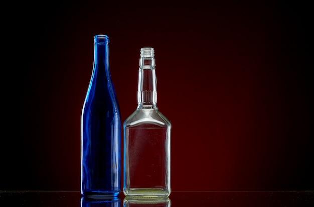 Dos botellas de alcohol vacías en rojo Foto Premium