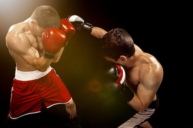 Dos boxeadores profesionales en la pared negra, Foto gratis