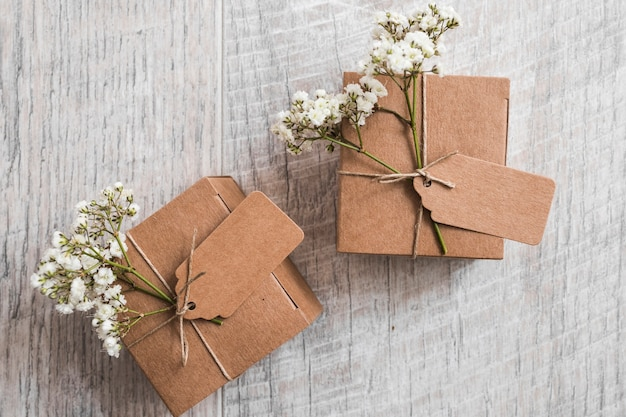 Dos cajas de cartón con etiqueta y flores de aliento de bebé sobre fondo de madera Foto gratis