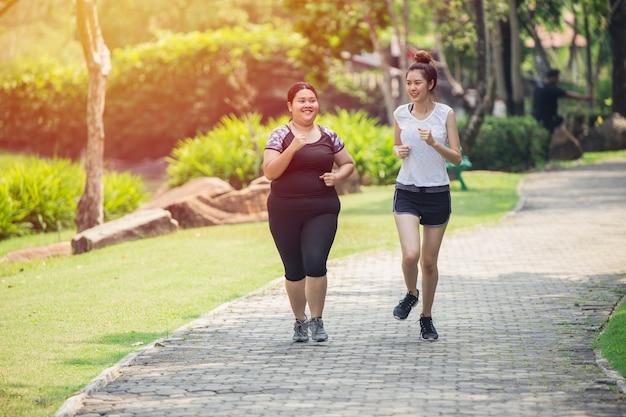 9150d604f98b Dos chicas asiáticas amigo gordo y delgado correr trotar en el ...