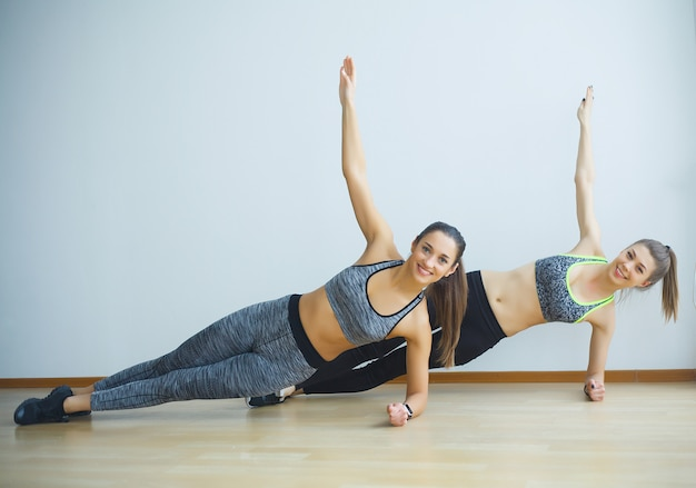 Dos chicas deportivas haciendo ejercicios ups en el gimnasio Foto Premium