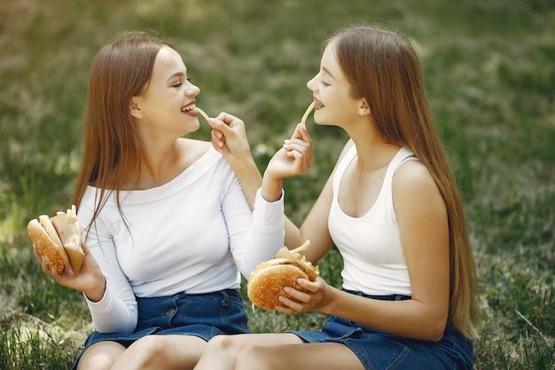 Dos chicas elegantes y con estilo en un parque de primavera Foto gratis