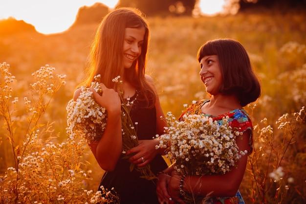 Dos chicas guapas con margaritas se paran en el campo Descargar
