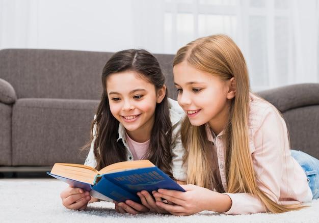 Dos chicas guapas tumbadas en la alfombra leyendo el libro juntas en casa Foto gratis
